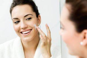 Beautiful woman applies serum for healthy skin