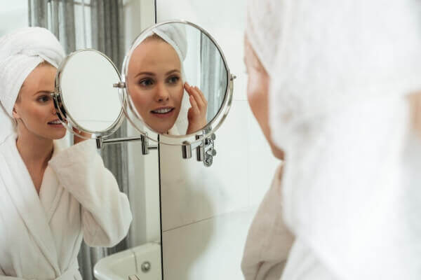 Woman applying serum on her face